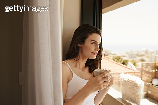 Shot of a beautiful young woman looking out of the window while having her morning coffee at home - gettyimageskorea