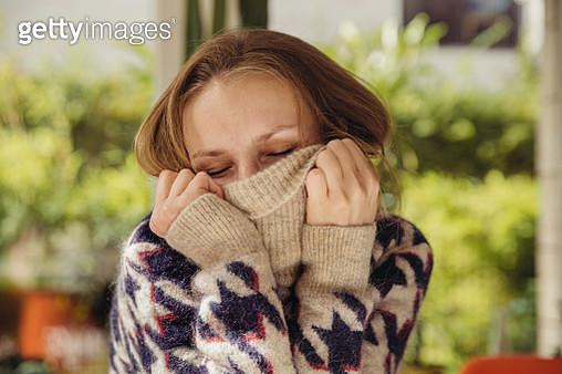 Portrait of young woman with closed eyes sinking in her woolen sweater - gettyimageskorea