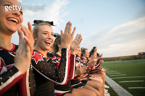 Smiling, enthusiastic teenage girl high school cheerleaders clapping on sideline at football game - gettyimageskorea
