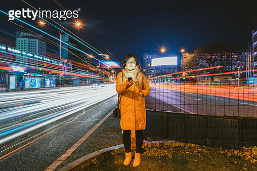 Young Asian Woman Using A Mobile Phone In Downtown District - gettyimageskorea