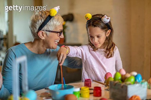 Happy beautiful little girl and gray hair grandmother prepare chicken eggs for holiday. Easter concept. - gettyimageskorea