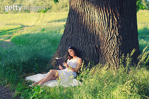 Young woman reading book in the summer nature - gettyimageskorea