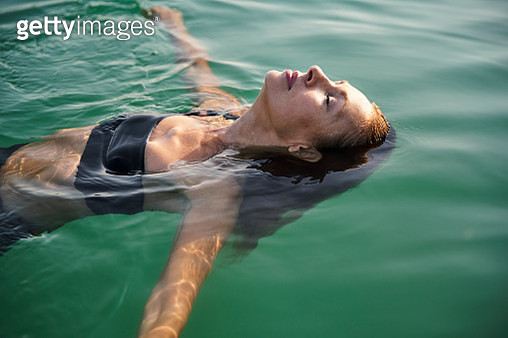 Mature woman floating in a lake with closed eyes - gettyimageskorea