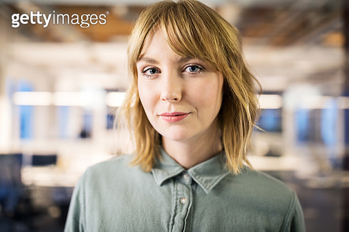Close up portrait of young businesswoman standing in modern office. Female professional in casuals. - gettyimageskorea