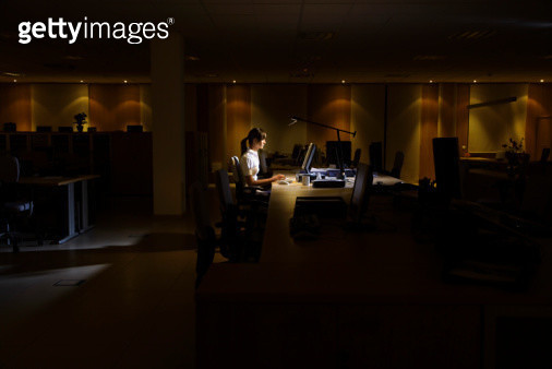 Woman Working in Dark Office - gettyimageskorea