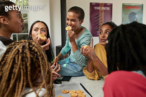 Happy friends talking while enjoying homemade cookies at kitchen - gettyimageskorea
