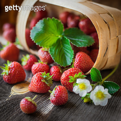 Strawberry Is Scattered From A Basket On A Wooden Background - gettyimageskorea
