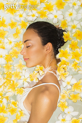 Glamour close-up woman portrait in spa bath full of uellow flowers. Beauty concept - gettyimageskorea
