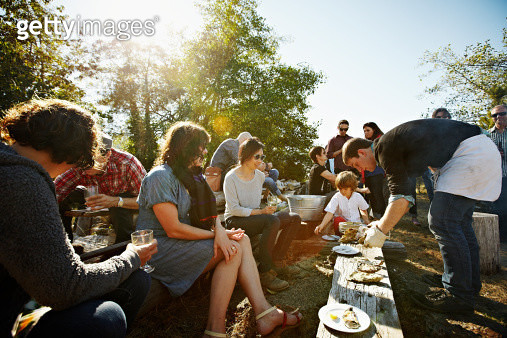 Group of friends and family eating oysters outside - gettyimageskorea