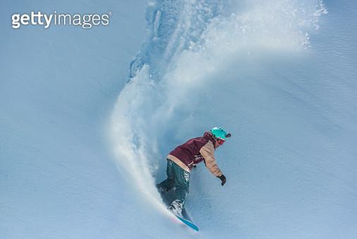 Snowboarder riding on powder snow - gettyimageskorea