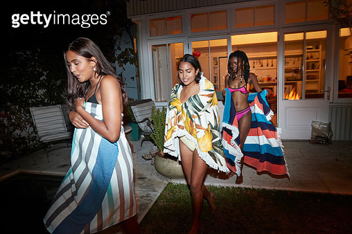 Multi-ethnic young female friends wearing towels walking in backyard at night - gettyimageskorea