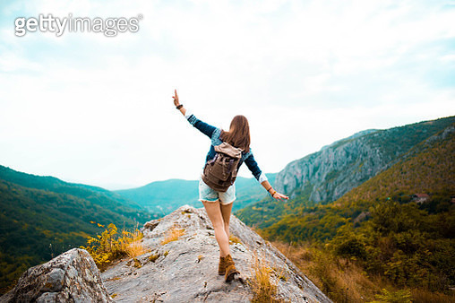 Young Hippie girl taking a walk on top of a mountain and enjoying the day. rear view - gettyimageskorea