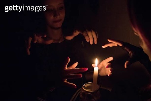 Women Practicing Witchcraft By Burning Candle In Darkroom - gettyimageskorea