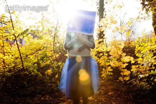 Blurred motion of child in blue dressing up costume against yellow Autumn foliage - gettyimageskorea
