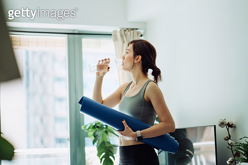 Confidence and determined young Asian sportswoman holding a yoga mat, refreshing with water after practicing yoga at home in the fresh bright morning. Fitness, wellness and healthy living concept - gettyimageskorea
