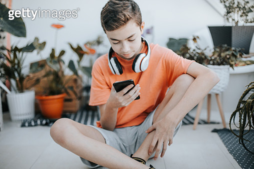 Teenage boy with headphones using mobile phone at table in room. 11 years old boy sitting behind a laptop and listening to music with headphones or playing video game. - gettyimageskorea