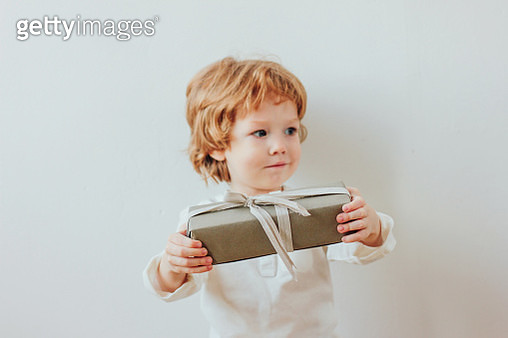 Boy Holding Christmas Present Against Wall - gettyimageskorea