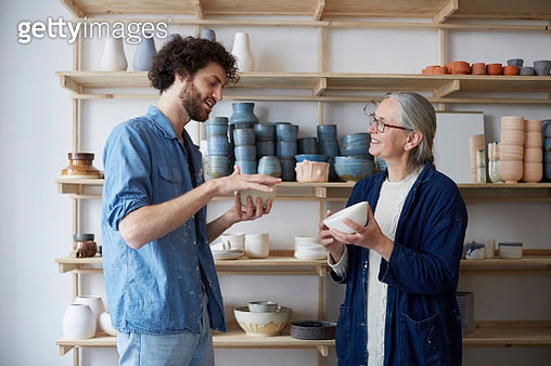 Man and woman discussing over bowl in pottery class - gettyimageskorea