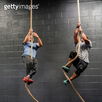 Two Latino athletes, the senior, 55-years-old, coach, and the young man climbing by a rope during the workout - gettyimageskorea
