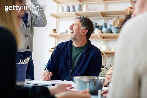 Smiling mature male student talking with female instructor in art studio - gettyimageskorea