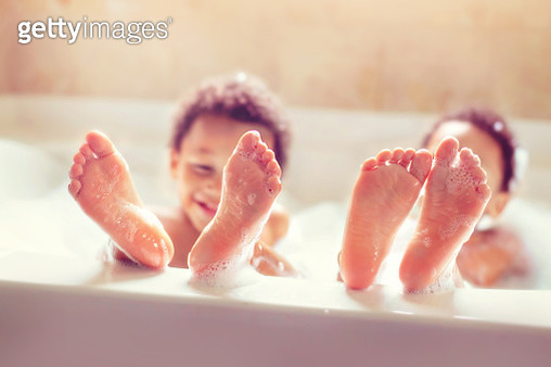 Twins showing off their bare feet in a bubble bath - gettyimageskorea