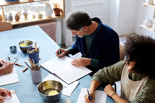 High angle view man and woman drawing at table during art class - gettyimageskorea