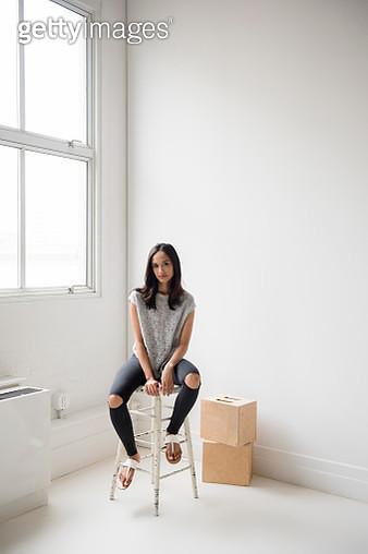 Mixed Race woman sitting on stool in corner - gettyimageskorea