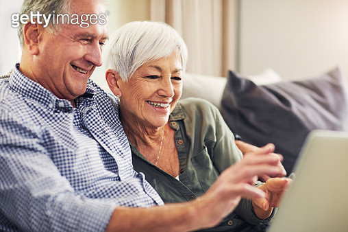 Shot of a waving senior couple using a laptop on the sofa at home - gettyimageskorea