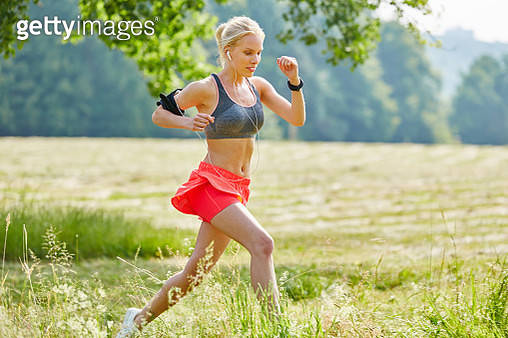 Young Woman Jogging On Grassy Field At Park - gettyimageskorea