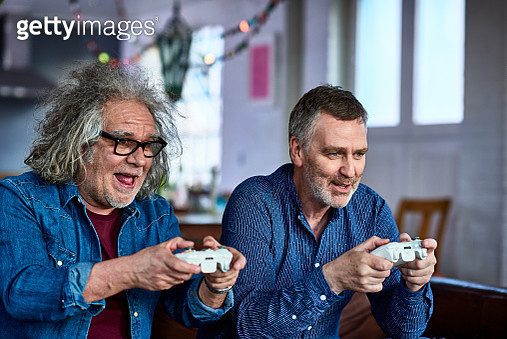 Two men using games consoles, gaming, connection, excitement, interactivity, focus - gettyimageskorea