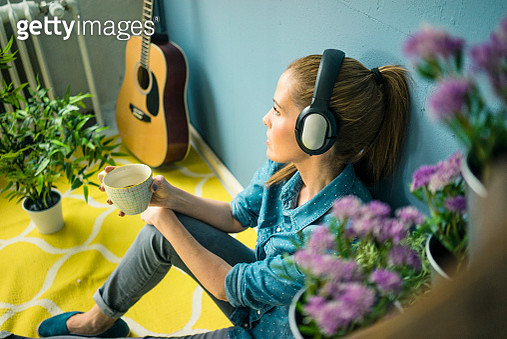Beautiful woman in her home, decorated with plants, listening music with headphones - gettyimageskorea