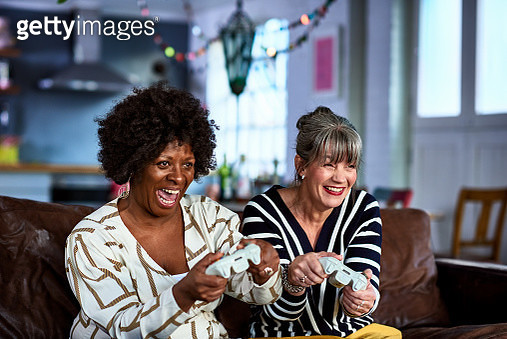 Mature friends playing on computer console, fun, excitement, leisure - gettyimageskorea