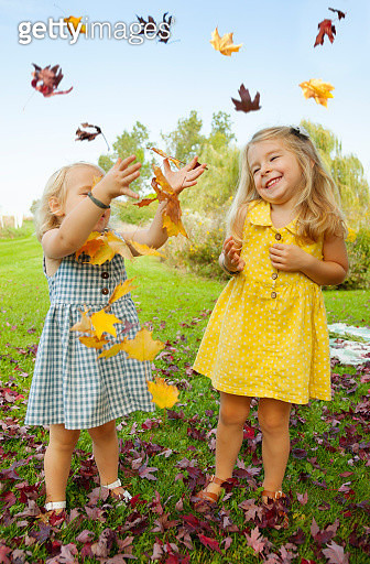 Little girls playing in leaves, discovering the splendor of Autumn - gettyimageskorea