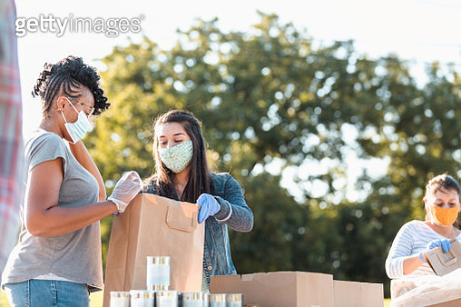 Young women discuss contents of bag at food drive - gettyimageskorea