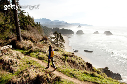 A woman hiking a secluded path along the coastline. - gettyimageskorea