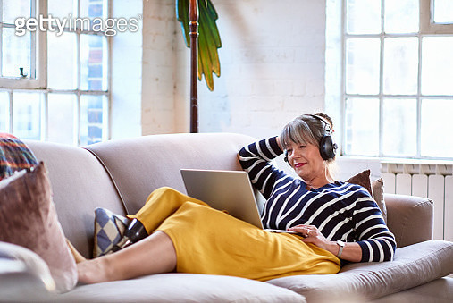 Senior woman wearing headphones watching movie on laptop - gettyimageskorea