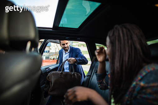 Young, handsome man entering a car, holding luggage, his friends sitting in car and waiting for him - gettyimageskorea