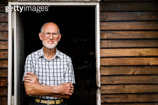 Portrait of confident senior male carpenter standing arms crossed at entrance of workshop - gettyimageskorea