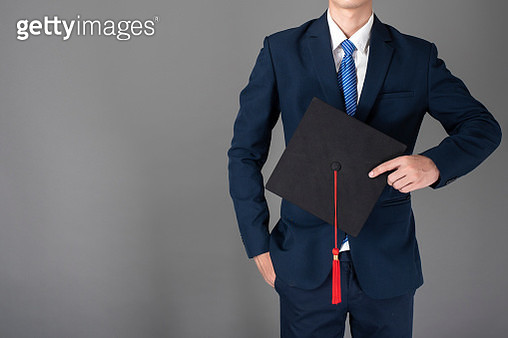 Midsection Of Businessman Holding Mortarboard Against Gray Background - gettyimageskorea