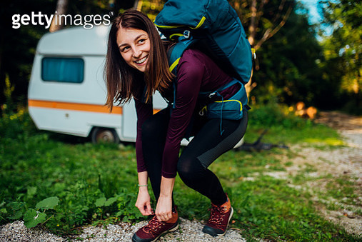 Young female hiker tying a shoelace and preparing for a hiking tour. - gettyimageskorea