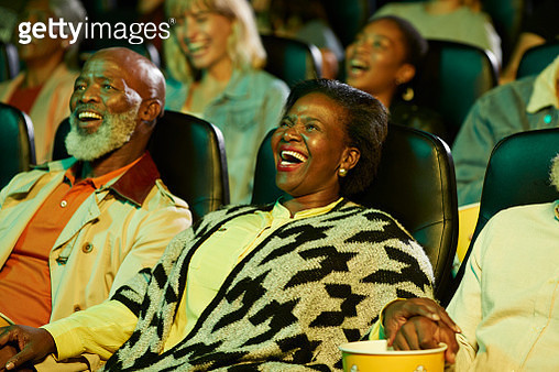 Cheerful male and female spectators enjoying comedy movie in cinema hall - gettyimageskorea