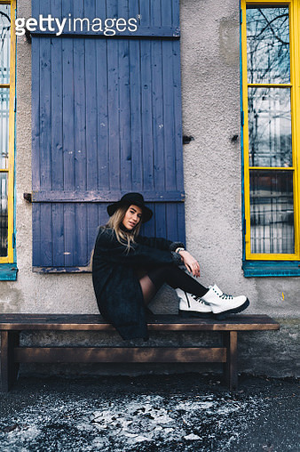 Long haired blond woman wearing a black fedora hat, a black coat with woollen lapels, and white boots, sitting on a wooden bench behind blue window shutters - gettyimageskorea