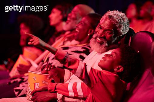 Smiling father looking at excited daughter watching movie in cinema hall - gettyimageskorea