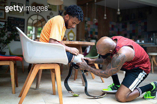 Personal trainer helping a young man with prosthetic leg - gettyimageskorea