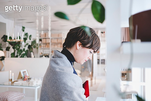 Side view of young female customer shopping in store - gettyimageskorea