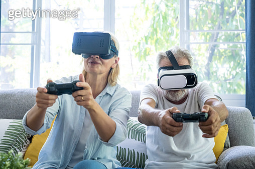 Happy senior couple playing virtual game together in the living room - gettyimageskorea
