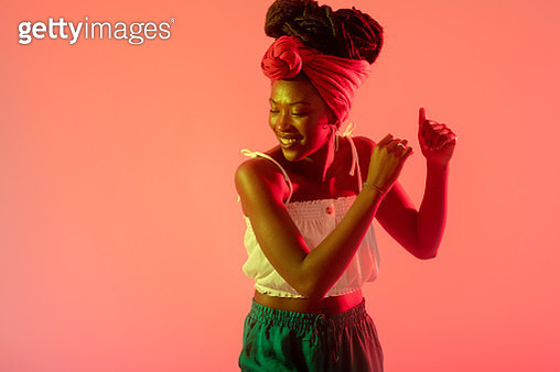 Woman with headscarf dancing against peach background - gettyimageskorea