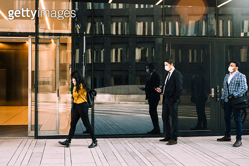 Business people with face masks standing in line outside office building - gettyimageskorea