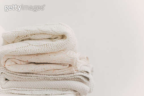Pile of beige woolen clothes on a white background. Warm knitted sweaters - gettyimageskorea