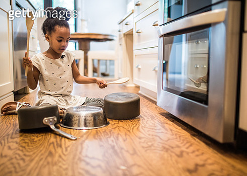 Young girl (6yrs) drumming on pots and pans in kitchen - gettyimageskorea